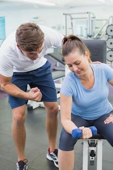 Osobisty trener pomaga klientowi podnosić dumbbell