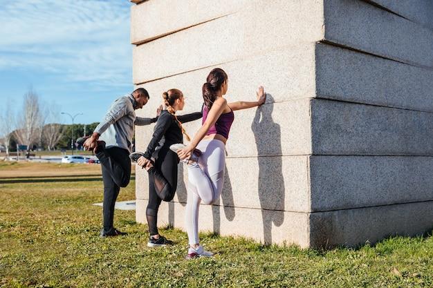 Osobisty trener rozciągający się z dwoma dziewczynami