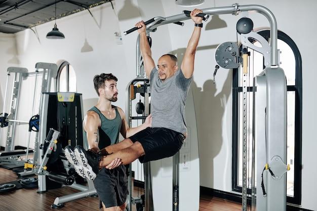 Osobisty trener sportowy kontrolujący podnoszenie prostych nóg przez klienta wiszącego na drążku gimnastycznym
