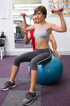 Osobisty trener z klientem podnoszącym dumbbells na ćwiczenie piłce