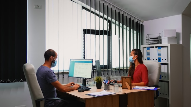 Osoby dezynfekujące ręce żelem alkoholowym przed pisaniem na klawiaturze. pracownicy pracujący w nowym normalnym biurze w firmie dezynfekujący ręce żelem antybakteryjnym przeciwko koronawirusowi.