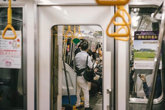 Osoby dojeżdżające do pracy pociągiem metra w środku idą do pracy