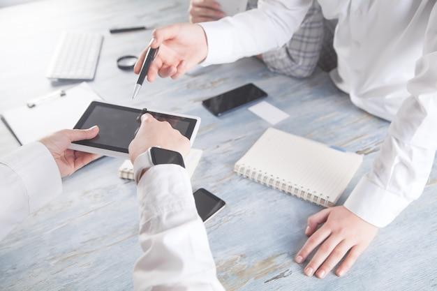 Osoby korzystające z cyfrowego tabletu w biurze.