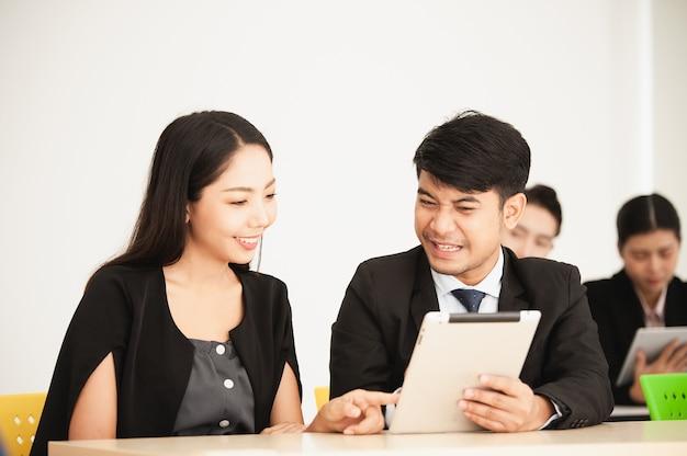 Osoby korzystające z tabletu rozmawiają w dyskusji na seminarium w klasie