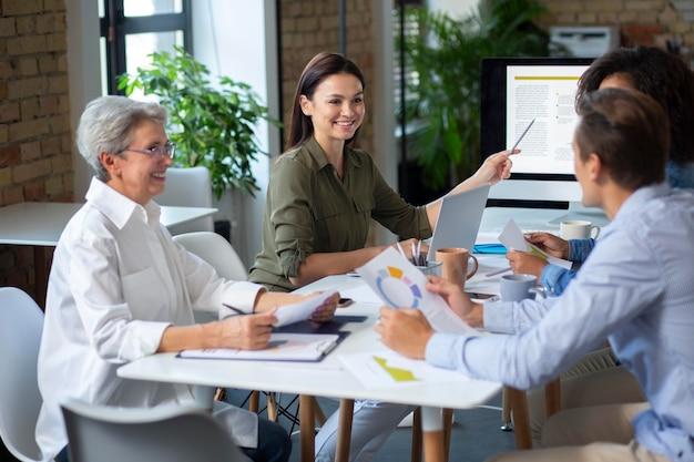 Osoby korzystające z urządzenia cyfrowego podczas spotkania