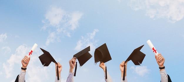 Osoby, które odniosły sukces w edukacji, trzymają czapkę maturalną na tle jasnego nieba z pięknem