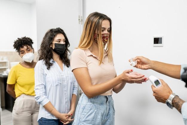 Osoby myjące ręce żelem wodnoalkoholowym przy wejściu do pracy w biurze
