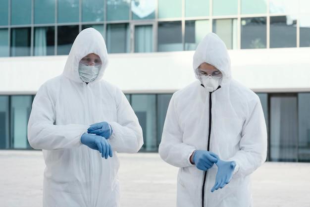 Osoby noszące kombinezony ochronne chroniące przed zagrożeniem biologicznym