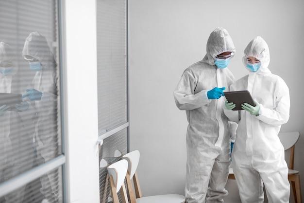 Osoby noszące kombinezony ochronne w strefie zagrożenia biologicznego