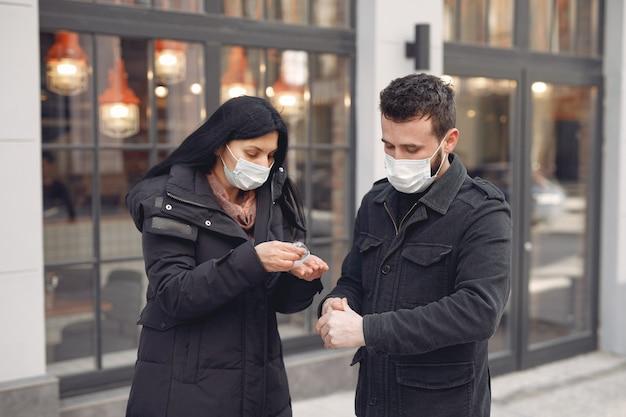 Osoby noszące maskę ochronną stojące na ulicy podczas używania żelu alkoholowego