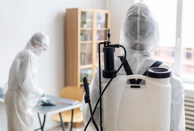 Osoby noszące sprzęt ochronny do dezynfekcji niebezpiecznego obszaru