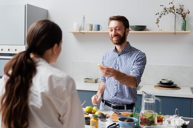Osoby o średnim ujęciach przygotowujące jedzenie w pomieszczeniu