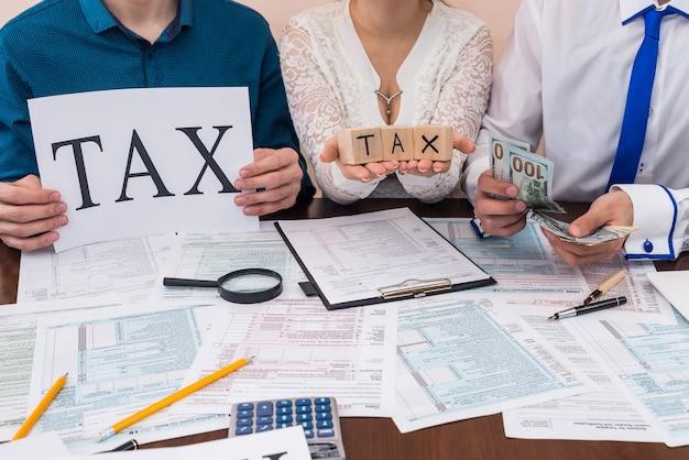 """Osoby pokazujące słowo """"podatek"""" i liczące pieniądze"""