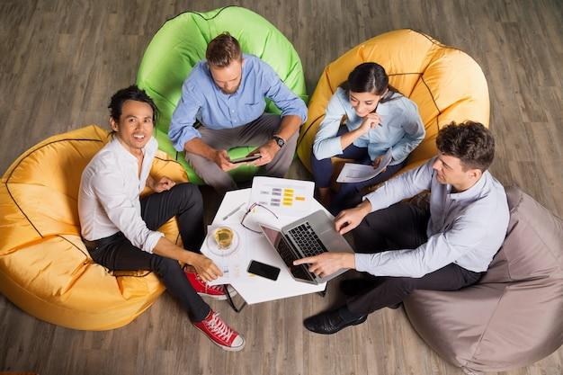 Osoby pracujące na krzesłach beanbag się modne pakietu office