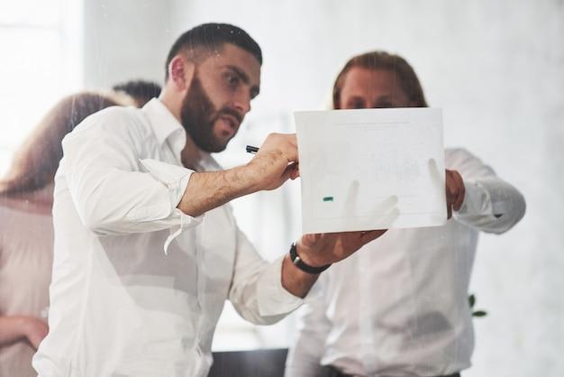 Osoby pracujące w biurze i omawiające niektóre szczegóły biznesowe z wykorzystaniem informacji na papierze