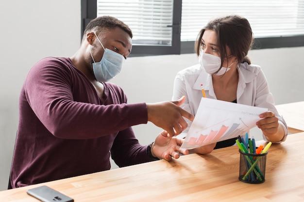 Osoby pracujące w biurze podczas pandemii z maskami medycznymi