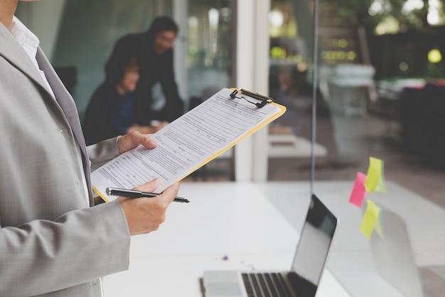 Osoby pracujące z dokumentem i komputer przenośny do wykorzystania jako koncepcja biura pracy
