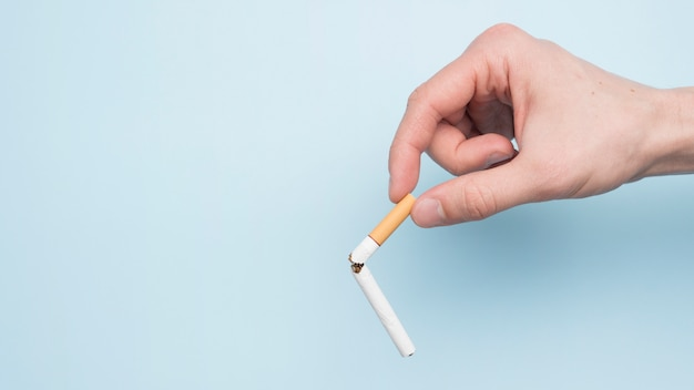Osoby ręka pokazuje łamanego papieros nad błękitny tło