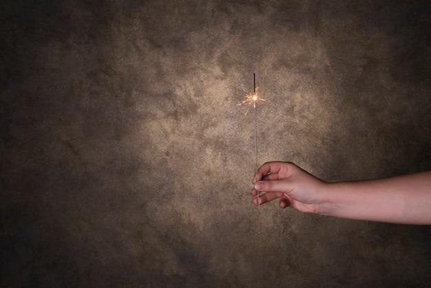 Osoby ręka trzyma płomiennego bengalia światło