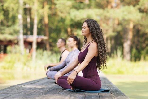 Osoby siedzące na macie w pozycji lotosu zajmują się medytacją na drewnianym moście w parku