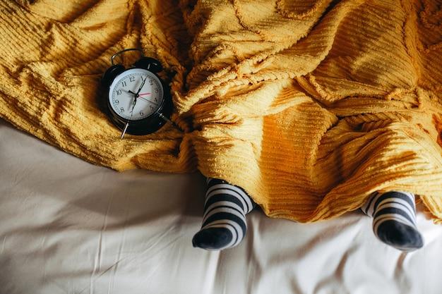 Osoby śpiące na łóżku pod kocami i ciepłymi skarpetami z budzikiem wskazującym godzinę 7 na boku
