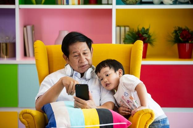 Osoby starsze lub dziadek i dzieci słuchające muzyki i grające w gry razem w salonie
