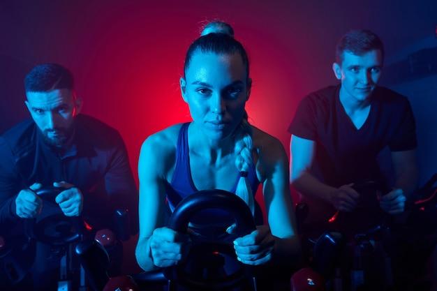 Osoby trenujące na rowerze stacjonarnym na siłowni, intensywny trening cardio. mężczyźni i kobiety w sportowym stroju trenujący razem, w zadymionej przestrzeni oświetlonej niebieskim neonem
