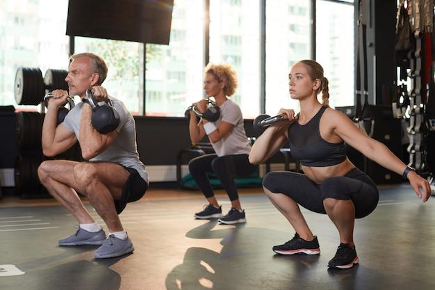 Osoby trenujące z hantlami podczas zajęć sportowych w klubie fitness