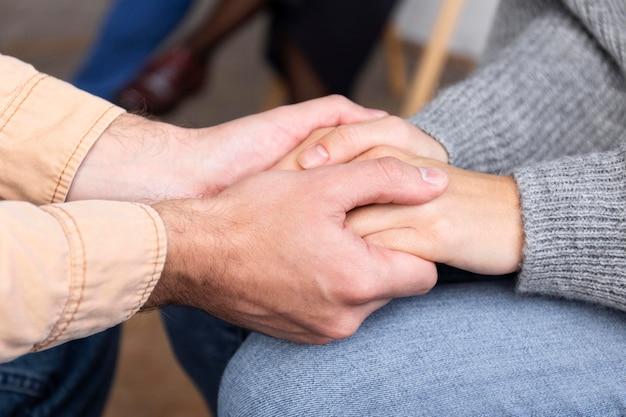 Osoby trzymające się za ręce podczas sesji terapii grupowej