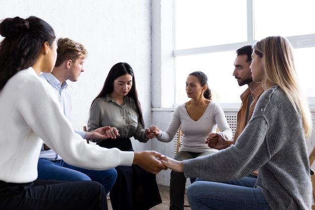 Osoby trzymające się za ręce w kręgu podczas sesji terapii grupowej