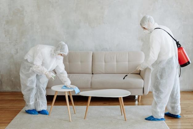 Osoby ubrane w kombinezon ochronny ze spryskiwaczem do dezynfekcji do dezynfekcji gospodarstwa domowego i mebli. pojęcie pandemicznej dezynfekcji koronawirusa lub covid-19. dezynfekcja pomieszczeń, domów