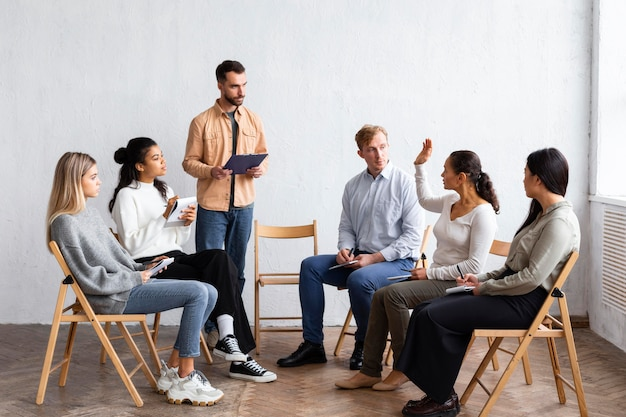 Osoby uczestniczące w sesji terapii grupowej siedząc na krzesłach
