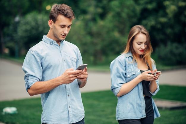 Osoby uzależnione od telefonów, para w letnim parku. mężczyzna i kobieta korzystający ze smartfonów, uzależnienie