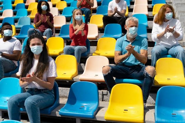 Osoby w maskach medycznych patrzące na grę
