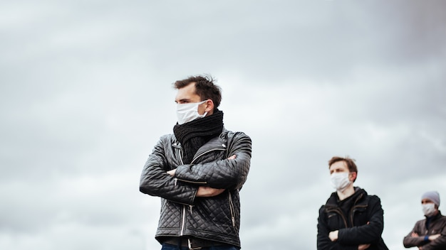 Osoby w maskach ochronnych stojące w bezpiecznej odległości. koncepcja ochrony zdrowia