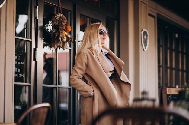 Osoby w podeszłym wieku bizneswoman w płaszczu na zewnątrz kawiarni