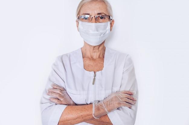 Osoby w podeszłym wieku dojrzałe kobiety lekarz lub pielęgniarka skrzyżowane ramiona w białym płaszczu medycznym, rękawiczki, maska na twarz sobie ochronny equiment na białym tle. pojęcie opieki zdrowotnej i medycyny. covid-1