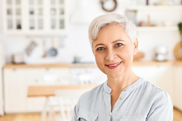 Osoby w podeszłym wieku, koncepcja dojrzałości i emerytury. urocza, wesoła europejska emerytka ubrana w zwykły strój, ciesząca się spokojnym porankiem w domu, w dobrym nastroju, czekająca na syna na śniadanie