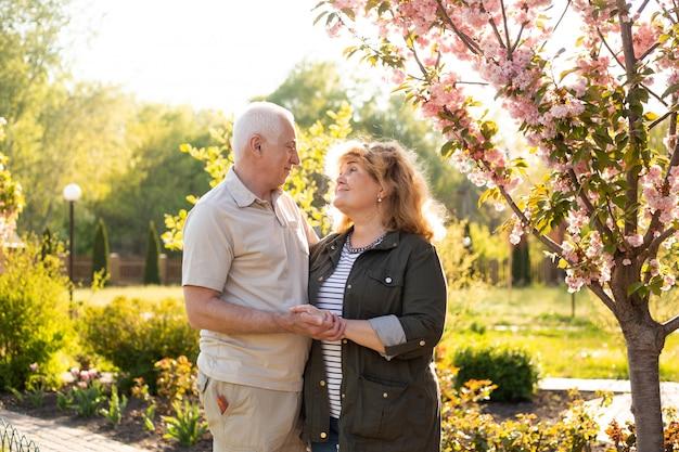 Osoby w podeszłym wieku para obejmującego w parku wiosną lub latem