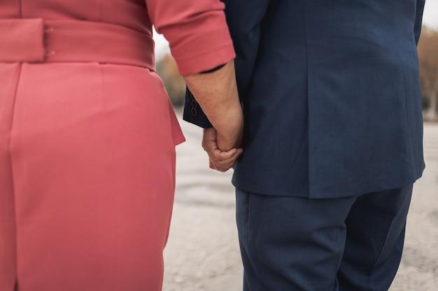 Osoby w podeszłym wieku para trzymając się za ręce i odwracając wzrok. zdjęcie zostało zrobione od tyłu. stare i piękne dłonie.