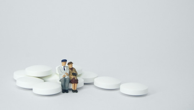 Osoby w podeszłym wieku postać siedząca na stosie białych tabletek.