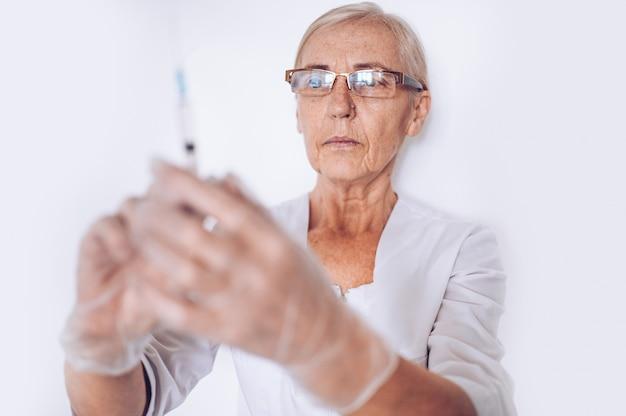 Osoby w podeszłym wieku starsza kobieta dojrzała lekarz lub pielęgniarka ze strzykawką w białym płaszczu medycznym i rękawiczki na sobie osobiste wyposażenie ochronne na białym tle. pojęcie opieki zdrowotnej i medycyny. kryzys pandemiczny covid-19