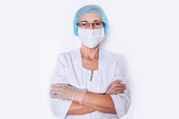 Osoby w podeszłym wieku starsza kobieta lekarz lub pielęgniarka skrzyżowane ramiona w białym płaszczu medycznym, rękawiczki, maska na twarz noszenie osobistego wyposażenia ochronnego na białym tle. pojęcie opieki zdrowotnej i medycyny.