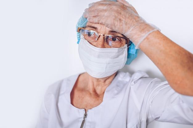 Osoby w podeszłym wieku zmęczone, wyczerpane starsze kobiety lekarz lub pielęgniarka, trzymając głowę w białym płaszczu medycznym, rękawiczki, maska na twarz, noszenie osobistego wyposażenia ochronnego. opieka zdrowotna i medycyna. kryzys pandemiczny covid-19