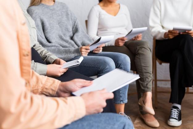 Osoby z zeszytami na sesji terapii grupowej