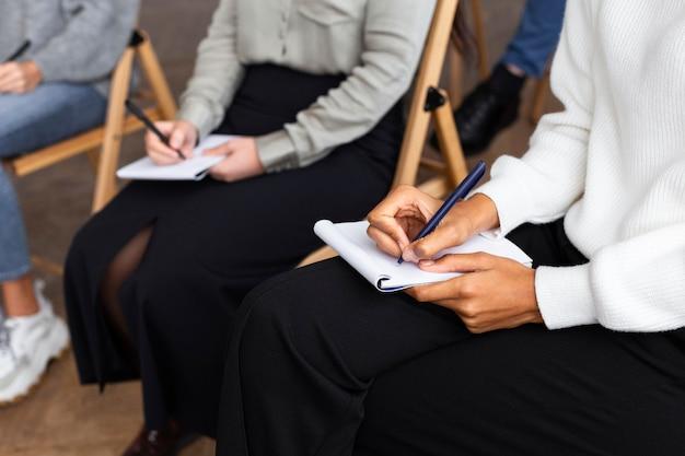 Osoby zapisujące w notatnikach podczas sesji terapii grupowej