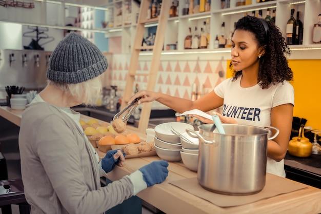Ośrodek dla bezdomnych. ładna, dobrze wyglądająca kobieta stojąca za stołem podczas serwowania jedzenia dla bezdomnych