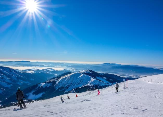 Ośrodek narciarski jasna w zimie na słowacji. panoramiczny widok ze szczytu ośnieżonych gór i stoku narciarskiego z narciarzami