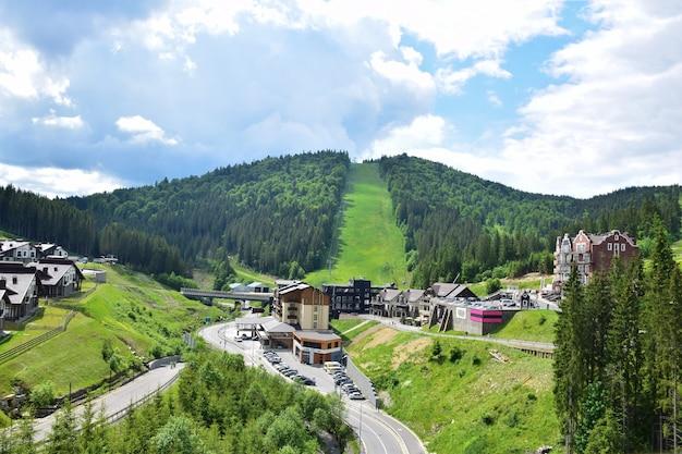 Ośrodek narciarski latem widok z lotu ptaka, w tle wyciąg do górykurort narciarski latem widok z lotu ptaka, w tle wyciąg do góry. góra pokryta jest lasem.