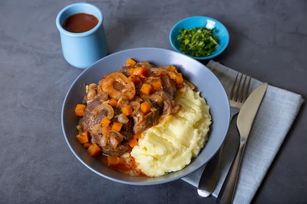 Osso buco. gicz cielęca (wołowa) z puree ziemniaczanym, gremolatą i sosem. tradycyjne włoskie danie. zbliżenie.